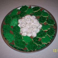 "Cookie Wreath Holly leaf sugar cookies arranged in a wreath, with royal icing pinecones. The cookies in the center are pecan sandie ""Snowballs""..."