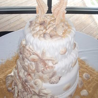 4 Tier Seashell White Fondant THIS CAKE HAD 115 WHITE CHOCOLATE SEA SHELLS AND A WHITE CHOCOLATE SEA HORSE BRIDE AND GROOM, uSED GRAHAM CRACKER FOR THE SAND