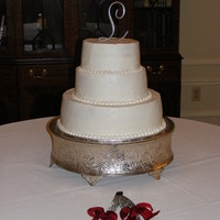 Simple, White Wedding Cake   3 tiered, round wedding cake with pearl border. Flowers were added later but the florist didn't show up before I left.