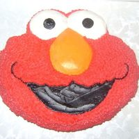 Elmo This is a simple Wilton pan cake. I baked two yellow layers and filled w/ raspberry cream. It smelled so good!