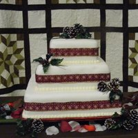 Christmas Wedding  Cake was done in a 8, 10, and 16 square. Frosted with Cream cheese frosting and Almond flavored Fondant. Pine cones, Holly and ribbon for...