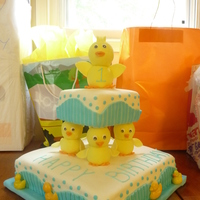 Yellow Ducky Marble cake with strawberry filling. Ducks are fondant covered globe pillars.Fondant embellishment on the sides. Chocolate molded ducks and...