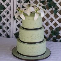"Sage Green With Lilies This cake consists of 12""x5"", 10""x5"" and 8""x5"" tiers. Iced with buttercream icing and trimmed with chocolate..."