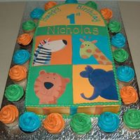 First Birthday Jungle Animals Cake is iced in bc with fondant squares and stripes with edible image animals. Hard to see in pic but animals have edible gliiter as do the...