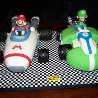 Mario 7 Luigi Kart Cakes  Had to make these both at the same time- double birthday . Wheels are RKT covered w/fondant, Figures are gum pate, The rest is yellow cake...