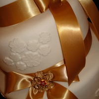 Gold Bows 6''-9''-12'' covered in white fondant, with gold bows and brooches.