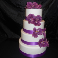 Purple Wedding Cake all covered in fondant artificial flowers.
