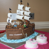 Pirate Ship Birthday Cake  Pirate ship made from vanilla chocolate chip with buttercream, fondant wood, treasure, cannon, wheel, railing. pirate figures are plastic....