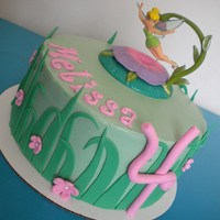 Tinkerbell Simple tinkerbell cake. Scratch WASC with raspberry whip cream filling, covered in SMBC with satin ice accents....