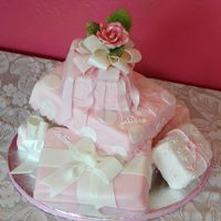 "Julianna Fondant covered ""packages"" with fondant/gum paste ribbons to celebrate her 1st birthday. Rose is gum paste"