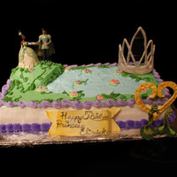 Frog Princess Birthday Cake covered in fondant, toy characters, and a royal icing crown
