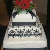 Black And White Damask And Quilted. Tier 1 and 3 are quilted with sugar pearl accent; Damask on flat fondant center tier, ribbons and jewel for accent, and a fresh flower...