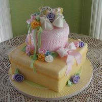Stacked Baby Gifts Embossed fondant covers both packages and the serving board. Sugarpaste baby shoes and braclet are nestled among ribbons and ribbon roses....
