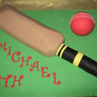 Cricket Bat 18Th Rich chocolate cake covered in dark chocolate ganaech, and rolled fondant.