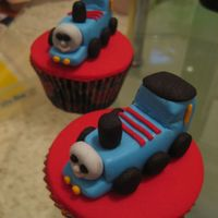 Thomas The Tank Engine Cupcakes Hand made Thomas the tank engine cupcake toppers on vanilla dairy free cakes. Made for party favours.