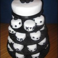 Black And White Engagment Cakes 30 mini mud cakes covered in fondant with black accents. Rolled Roses on top of large cake. Couples initals on smaller cakes.