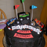 Monster Truck Tire Mud tire, with monster truck toys.. Buttercream frosting, decorations withfondant. Chocolate cake.
