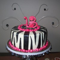 Hot Pink And Black Zebra Striped Cake   Done for a 13 year old. Iced with buttercream and decorated with fondant accents.