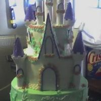 Castle Cake  This is a 3-tiered castle cake, iced in buttercream, the small flowers are made from Wilton's fondant and Wilton's flower cut-out...