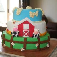 Down On The Farm Our son's 1st birthday cake. It is a three tier farm theme. Top and bottom tier svanilla with white buttercream, middle tier chocolate...