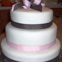 Baby Shower Cake Pink and Brown theme. Three tiered (vanilla, chocolate and strawberry) cover with buttercream and fondant. Polka dot ribbon to match the...