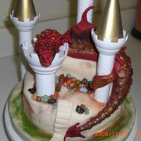 Dragon And Castle Dragon is made out of fondant and draped onto the cake!