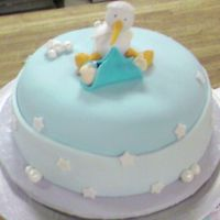 "Baby Stork Watching Over A Baby 6"" round with pastel blue fondant with a fondant cloud border and fondant stars and bubbles covered with silver luster dust topped..."