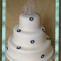 White 3 Tier Wedding Cake White 3 tier wedding cake with blue pearl dusted flowers.