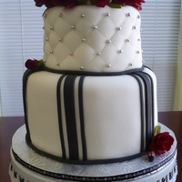 Black And White Wedding Cake Cake is french vanilla with buttercream icing and covered with fondant. Accents and roses are fondant/gumpaste. TFL!