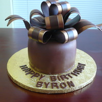 Byron's Birthday Cake Chocolate cake covered with chocolate ganache and covered with chocolate fondant. Bow is fondant/gumpaste with bronze luster dust. TFL!