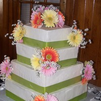 Gerbera Daisy Wedding Cake Loved the color scheme for this cake! White chocolate cake with white chocolate buttercream. Added artificial flowers and ribbon. Bride...