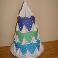 White Christmas Layers are covered in blue, green and purple fondant. The trees are cut from fondant and dried, then branches piped in royal icing. The...