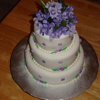 60Th Birthday Cake fonant covered cake with small fondant and royal icing flowers. The flowers on top are silk.