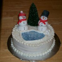 Snowman Cake buttercream cake with fondant snowpeople. Lake is blue fondant with luster dust. The tree is an upsidedown sugar cone piped with...