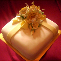 White Gift Wedding Cake This is a buttercake with white fondant and sugar paste flowers. The bride asked for white and light yellow as the color theme.