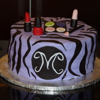 Purple Zebra Cake With Makeup Theme purple buttercream with black zebra striped made out of fondant. Makeup made with fondant as well. Cake was chocolate cake with a fresh...