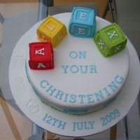 Christening Cake - Building Blocks This was a cake that I made for my friend's sons christening. I used stencils for the feet with royal icing.