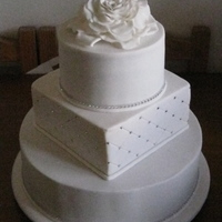 White Wedding - With Bling Dark chocolate, white chocolate and caramel mudcakes covered in white fondant. Swarovsky crystals added as bling. Large rose topper made...
