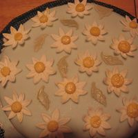Final Cake For Gumpaste Fondant Class Blue covered fondant cake with daisys covering cake a few leaves added for color.