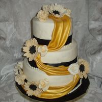 Black And Gold Chocolate WASC and regular WASC with chocolate cream filling, IMBC under fondant . All fondant and gumpaste flowers. Fondant swag in gold....