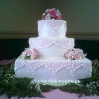 "Elegantly Pink The cake sizes are a 14"" square cake with a 10"" and a 6"" round on top. This cake will serve 125. It was iced with a non-..."
