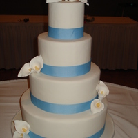 Calla Lilly Wedding Cake White fondant wedding cake with Gumpaste Calla lillies and cornflower blue ribbon accents