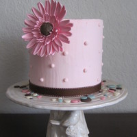 Pretty And Pink! 6 inch round cake that is also 6 inches tall. Covered in buttercream and decorated with a single 4 inch round gumpaste gerbera daisy. This...