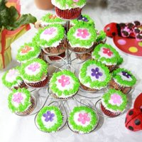 Cup Cakes With Flowers Cup cakes with buttercream icing and the little flowers are fondant.