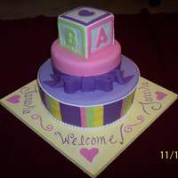 Welcome Janavia three tier cake, including baby block on top. Fondant and royal icing accents.