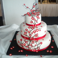 A Cherry Blossom Affair... 3 tier red velvet, cream cheese filling and raspberry flavored fondant...hand painted gumpaste blossoms...a great success!!