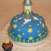 Rocket Cake Chocolate cake with coordinating chocolate cupcake. Rocket is sculpted from rice krispies and covered in fondant and gum paste.