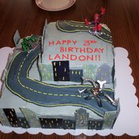 Spiderman Saves The City Spiderman birthday cake for a three year old boy. buildings on the sides of the cake are made of fondant.