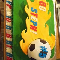 Flaming Soccer Ball 12x18 yellow cake. Cake ball covered in fondant. Cardboard flame covered in fondant. For my friend's daughter -- it is her team's...