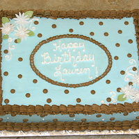 Blue & Brown Polka Dots 1/2 sheet of french vanilla cake with chocolate ganache filling, iced in buttercream with fondant daisies.